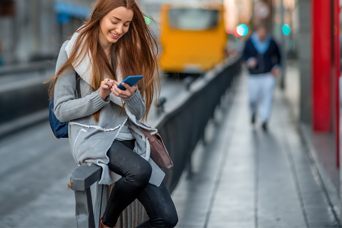 """Woman with phone in the city """"width ="""" 1200 """"height ="""" 800"""
