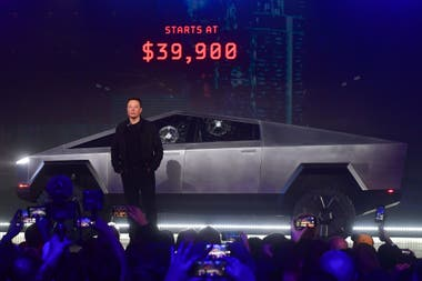 Elon Musk with his Tesla Cybertruck; the side glass splintered after he hit them with a ball