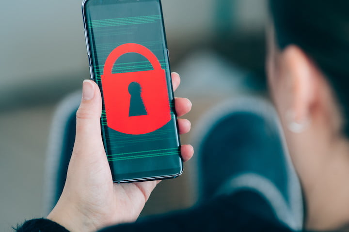 A woman looks at the screen of her Android phone, which has a large red padlock | How to activate safe mode on Android