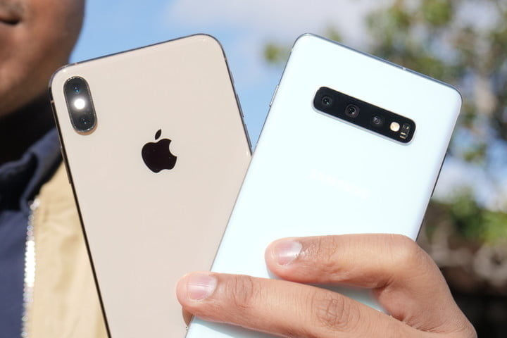 A man holds the iPhone XS Max and the Galaxy S10 phones in one of his hands