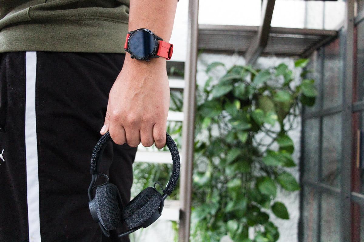 User holding Adidas RPT-01 wireless headphones