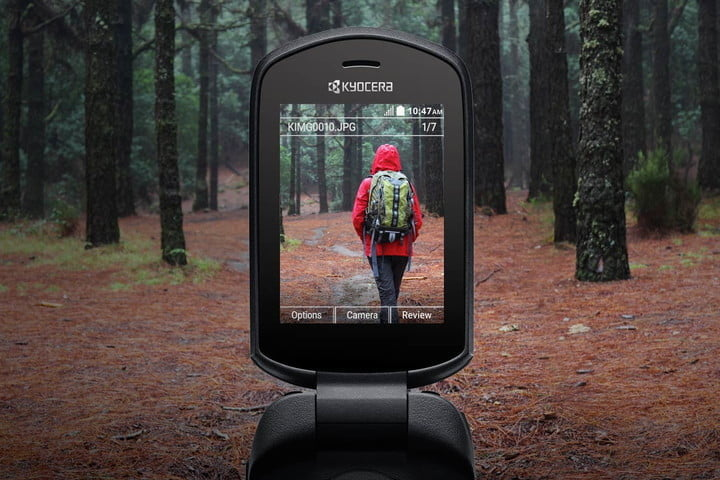 a phone screen taking a picture of a person with roha jacket and a bag in the woods