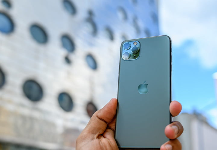 A person holds an iPhone 11 Pro Max phone in the street. We explain how to restore an iPhone from the factory