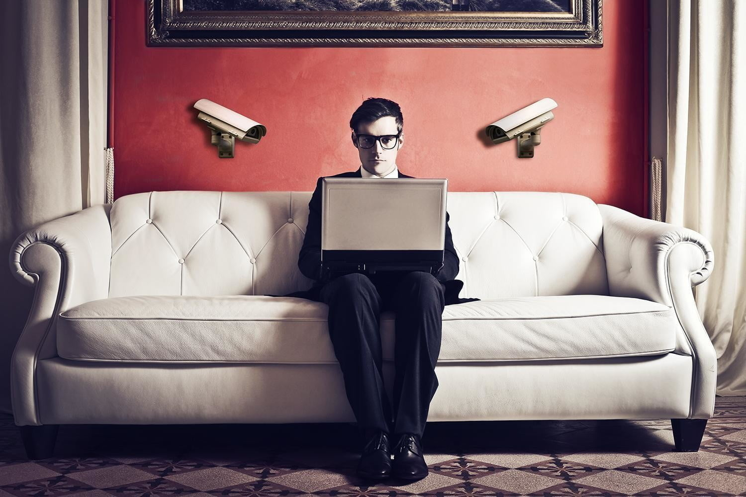 A man in black sitting on a couch looking at his computer with a worried face | How to delete cookies on different devices