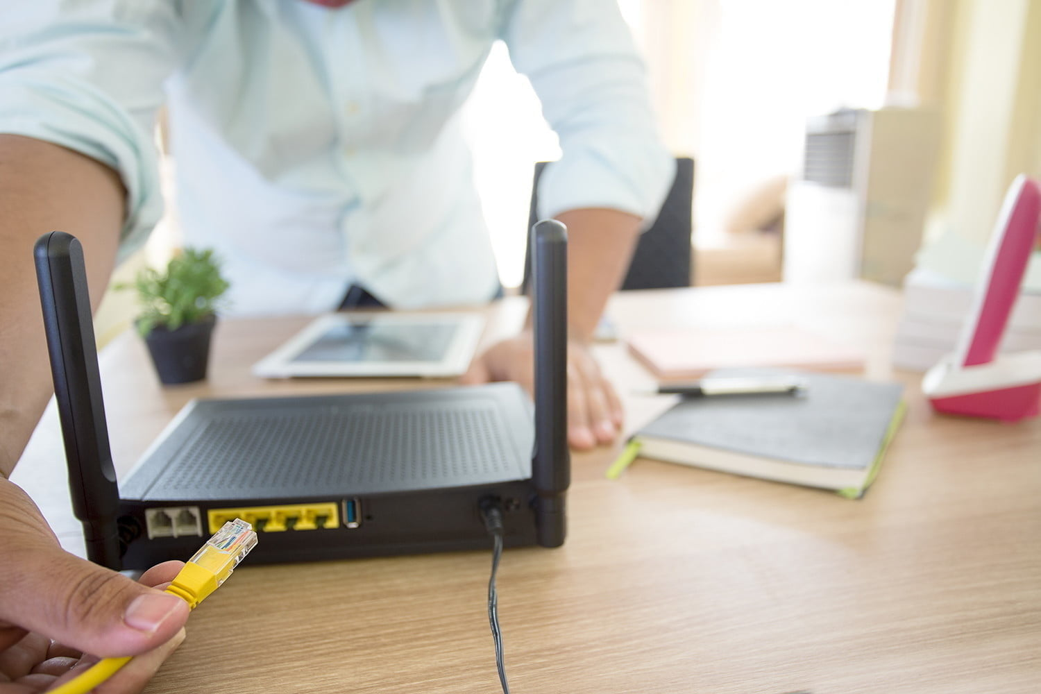 A person connects an ethernet cable to the back of a router | How to know the router's IP
