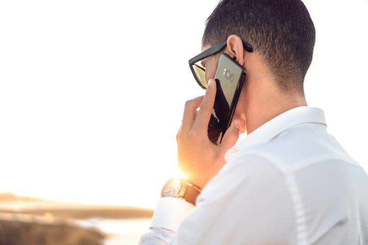Person dressed in white shirt making a call with his cell phone