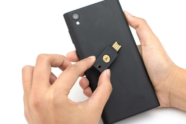 Hand holding a YubiKey 5 NFC on his cell phone to access