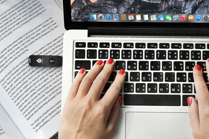 Woman's hands using a laptop keyboard and one of the best USB security keys installed on the left side