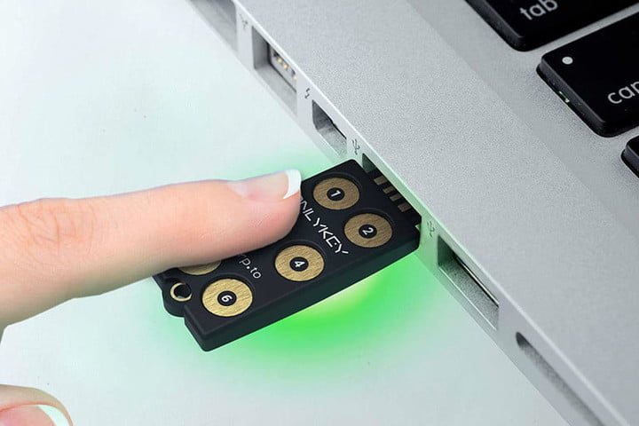 A finger touching a CryptoTrust OnlyKey USB security key that is inserted into a laptop