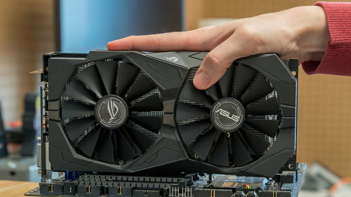A hand holding an AMD Radeon RX570 video card, one of the best graphics cards for video editing