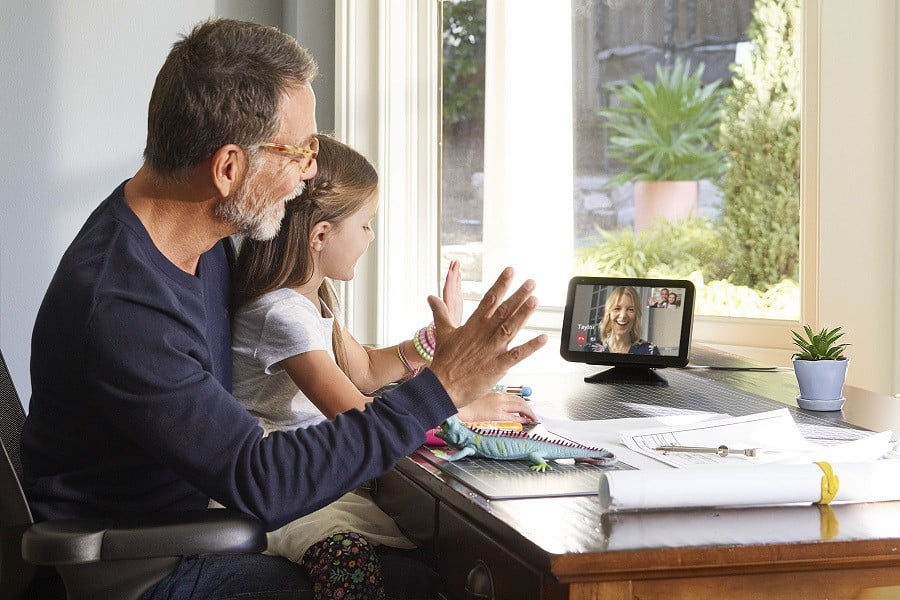 A girl sitting on her father's lap at home talking to her mother using an Amazon Echo Show device with an 8-inch screen