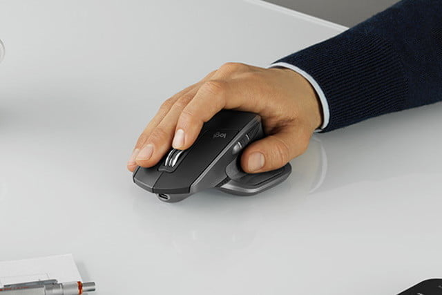 The hand of a person working with the Logitech MX Master 2S on a white table