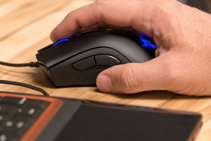 A person's hand on the Razer DeathAdder Elite mouse and its blue illuminated logo and on one side a part of a laptop