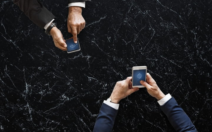 Top view of two people while they check their cell phones to configure VoIP service in their company