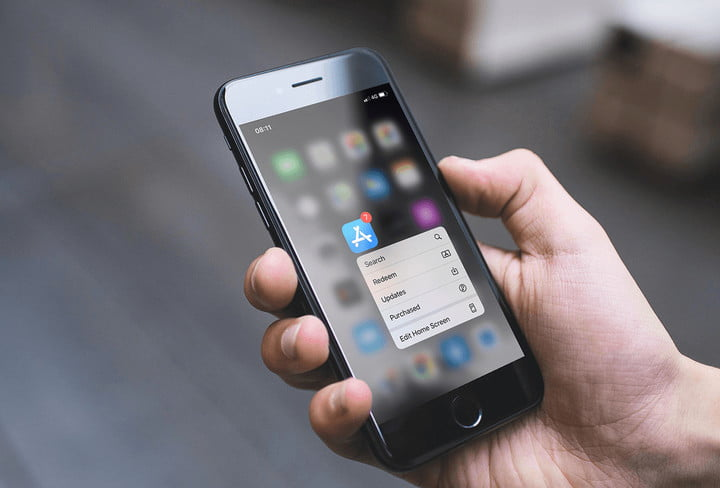 A person's hand with a cell phone in his hand making changes to know how to hide apps on iPhone
