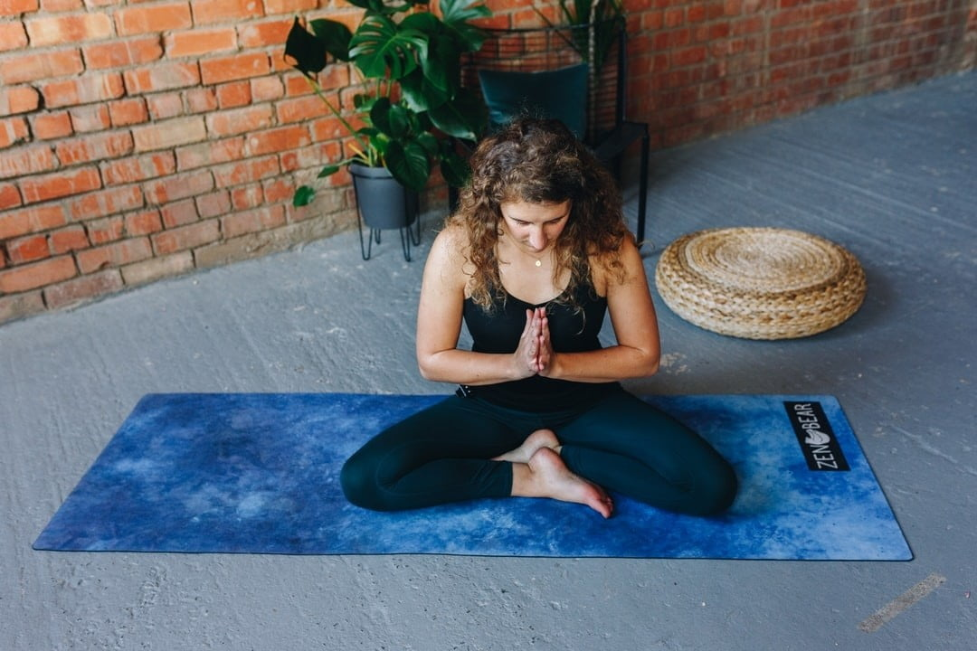 A woman practices yoga in a living room with one of the best
